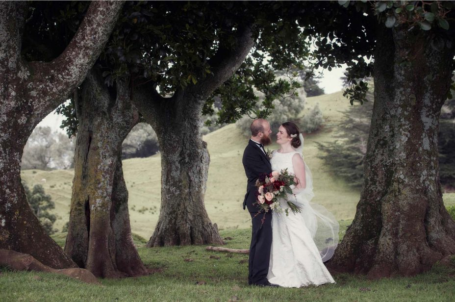 Bride and groom look into each other's eyes smiling for a wedding photo in Cornwall Park Auckland.