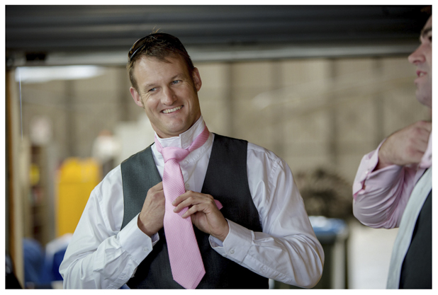 Groomsmen gets ready for a wedding knots his pink tie at Whenuapai airbase Kumeu.
