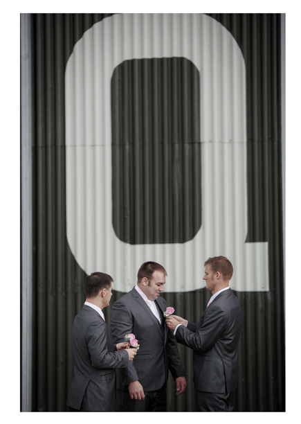 Groomsmen get ready for a wedding as they put on buttonhole flowers at Whenuapai airbase Kumeu.