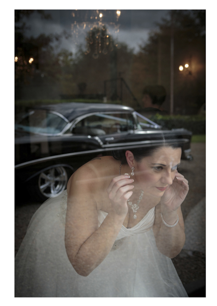 Bride adjusts her earing using her reflection in a windown