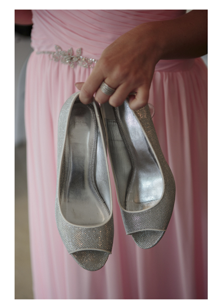 Close up photo of Bridesmaid's silver slip-on shoes against her pink pleeteddress