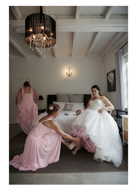 Bridesmaid in dusty pink pleated dress helps bride in full white dress to put her wedding shoes on.