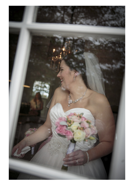 Bride wearing her wedding dress holding her floral bouquet photographed through window frame