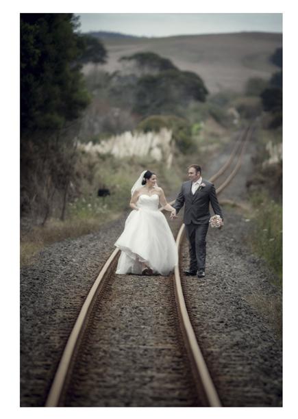 Bride in wedding dress walks with groom along romantic disused railway line in Kumeu.