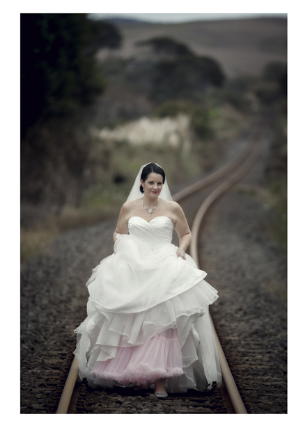 Bride in wedding dress walking along romantic disused railway line in Kumeu.