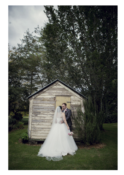 Bride in wedding dress embraces groom pose for a photo by rustic shed in Kumeu.