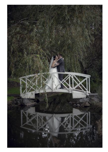 Bride and groom pose on Romeo and Juliet bridge.