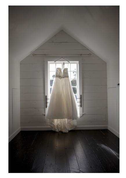 Full length wedding dress hangs in pretty sash window