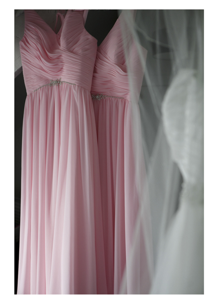 bride's dress hangs next to with pink pleated bridesmaids dresses.