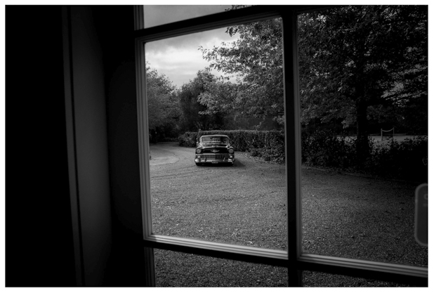 black and white photo of classic american wedding photographed through window frame