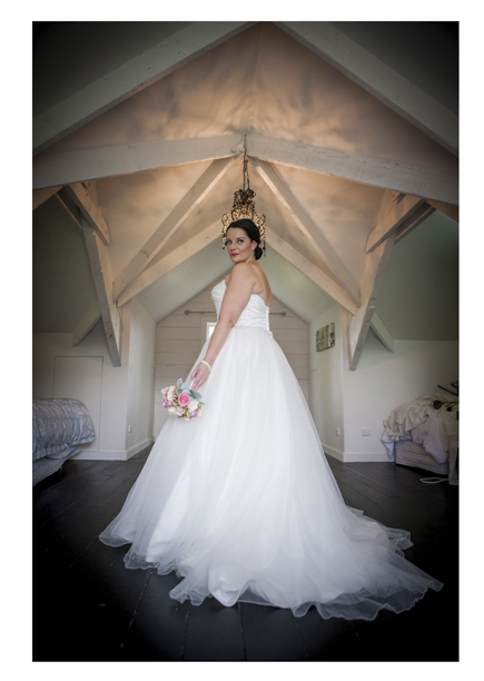 Bride in fluu wedding dress poses for a photo in a room with a vaulted ceiling.