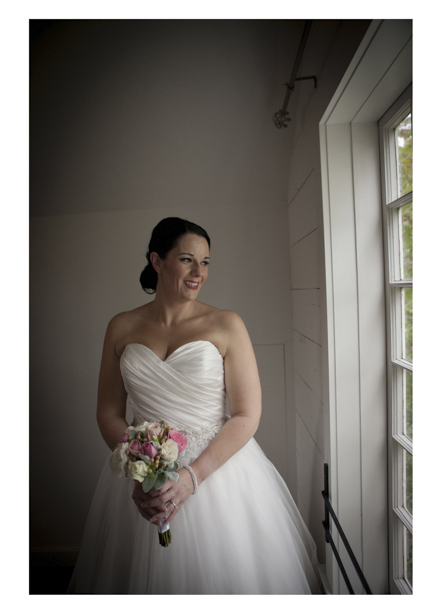 Bride in white dress poses for photo by window