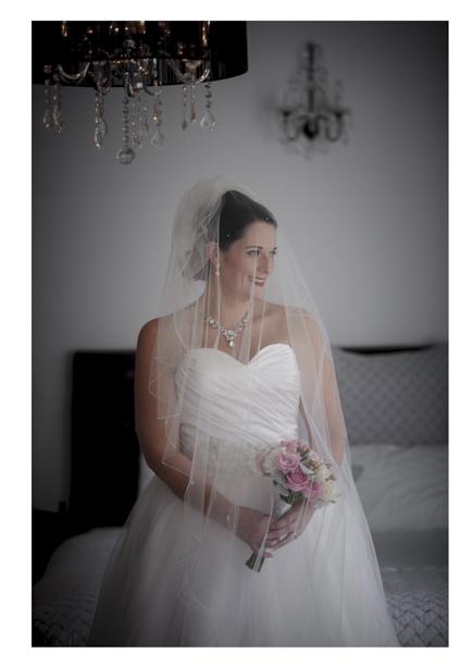 Bride in white wedding dress poses my sash window at Gracehill Vineyard Estate