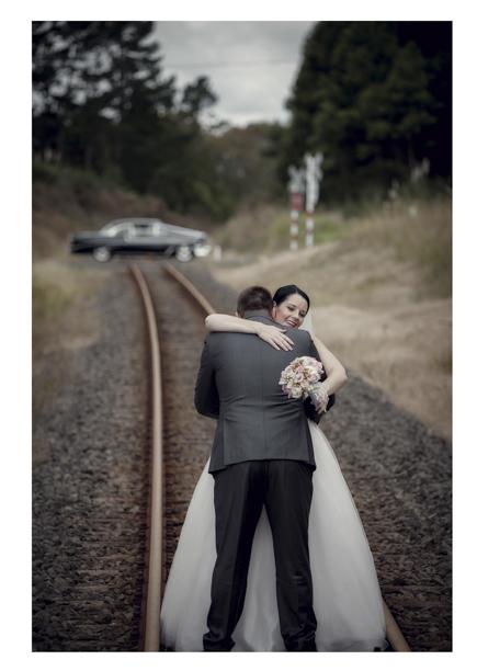 Bride in wedding dress embraces groom along romantic disused railway line in Kumeu.