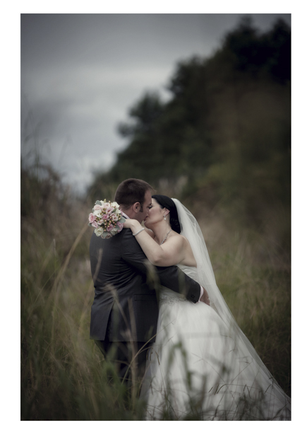 Bride in wedding dress embraces groom in long grass by a romantic disused railway line in Kumeu.