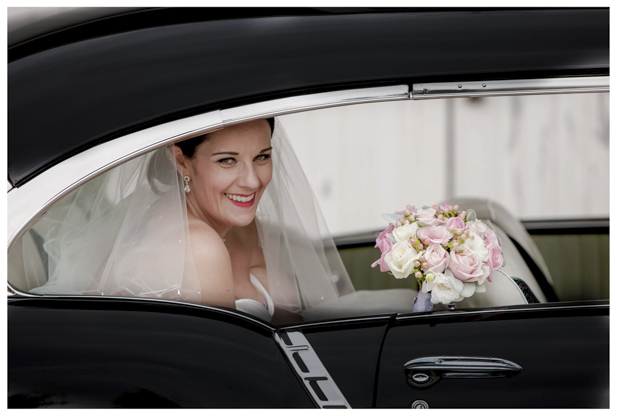 Bride holding flower bouquet sitting in the back of classic wedding car .