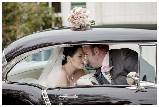 Bride holding flower bouquet and groom sitting in the back of classic wedding car .