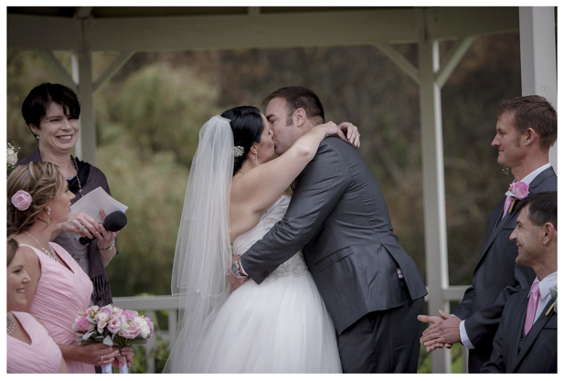 Bride and groom first kiss during wedding ceremony at Gracehill Vineyard Estate