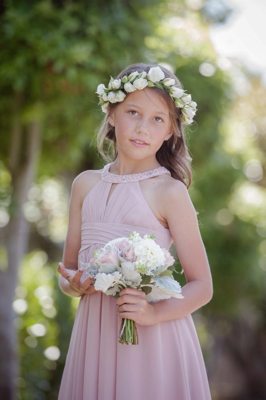 Bridesmaid girl in pink dress poses at wedding in Auckland sunshine