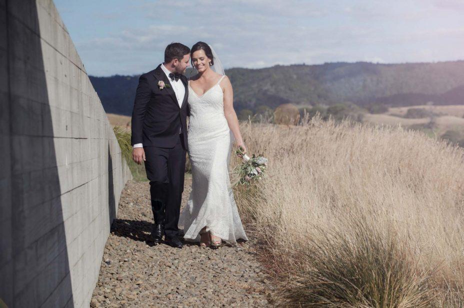 Black & white photo Bridegroom watches wife make speechBride & groom walk in afternoon summer sunshine at KBB Kauri Bay Boomrock Auckland