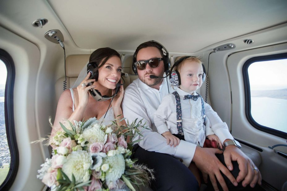 Bride, groom and their son look out of helicopter Me window on their way to wedding reception at KBB Kauri Bay Boomrock