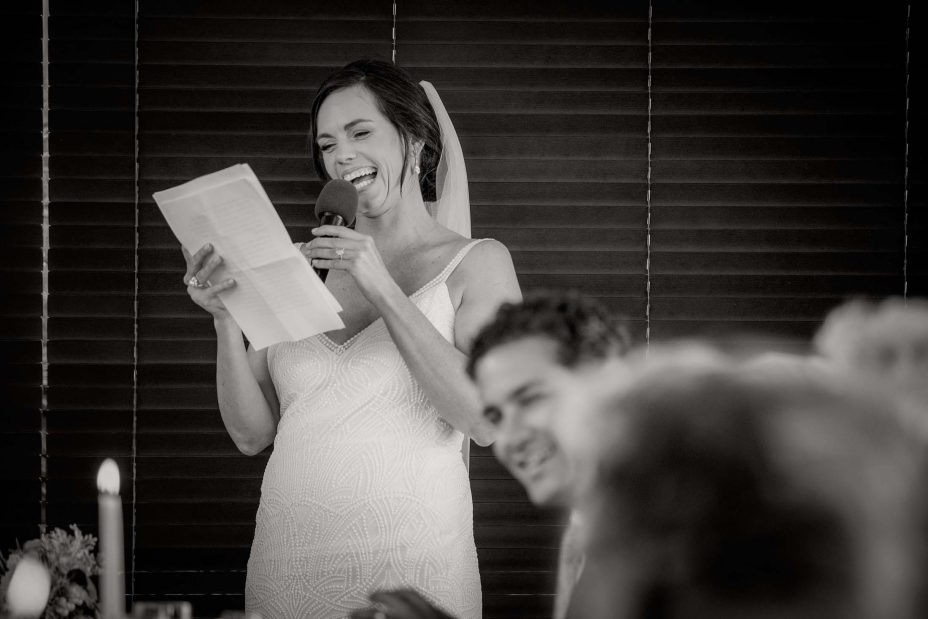Bride and groom laugh at speBride laughs as she makes speech at her wedding reception at KBB Kauri Bay Boomrock