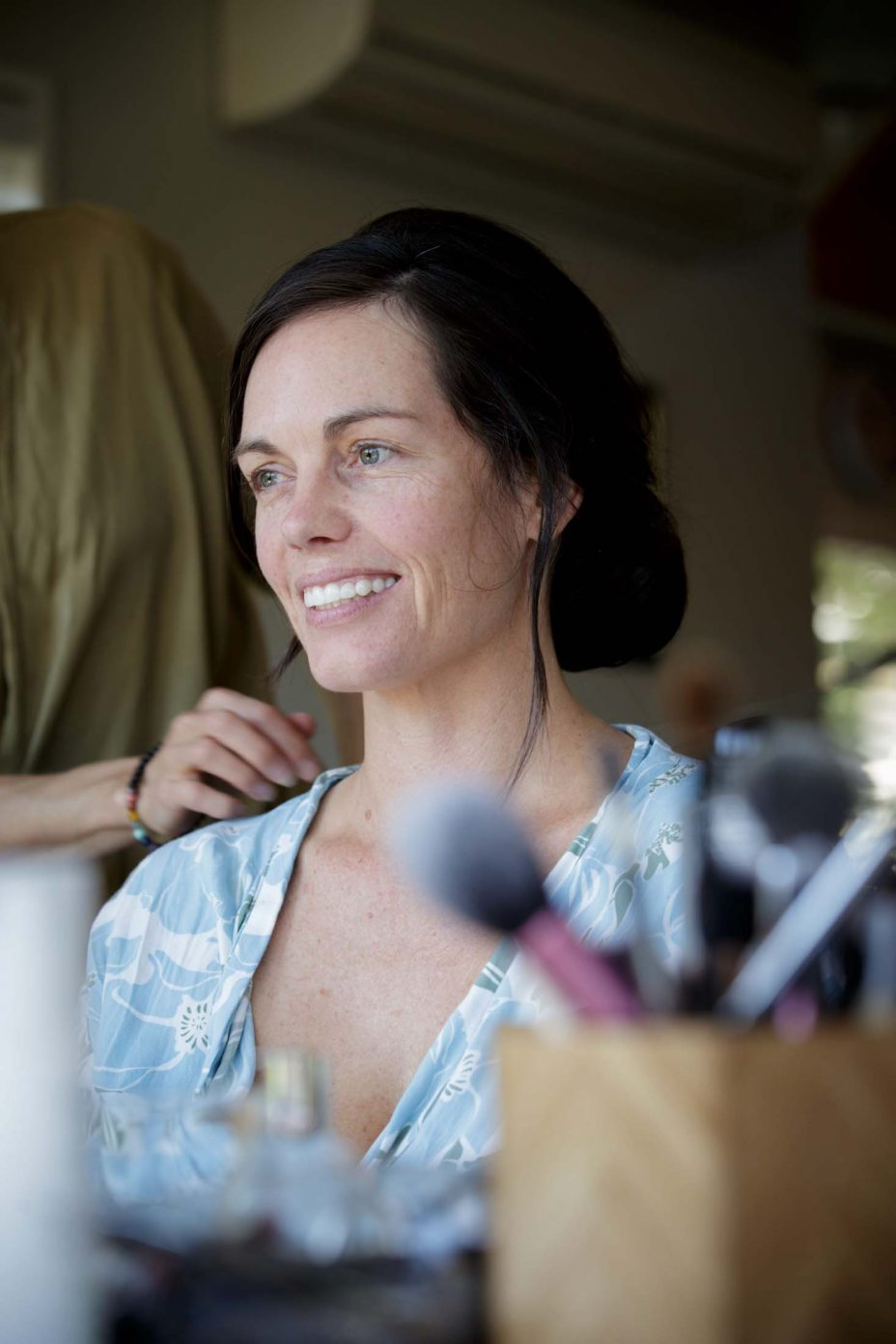 Bride in blue robe smiles during makeup preparations