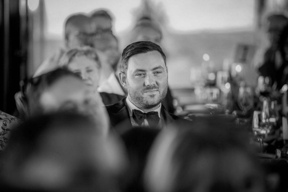 Black & white photo Bridegroom watches wife make speech at their wedding reception at KBB Kauri Bay Boomrock