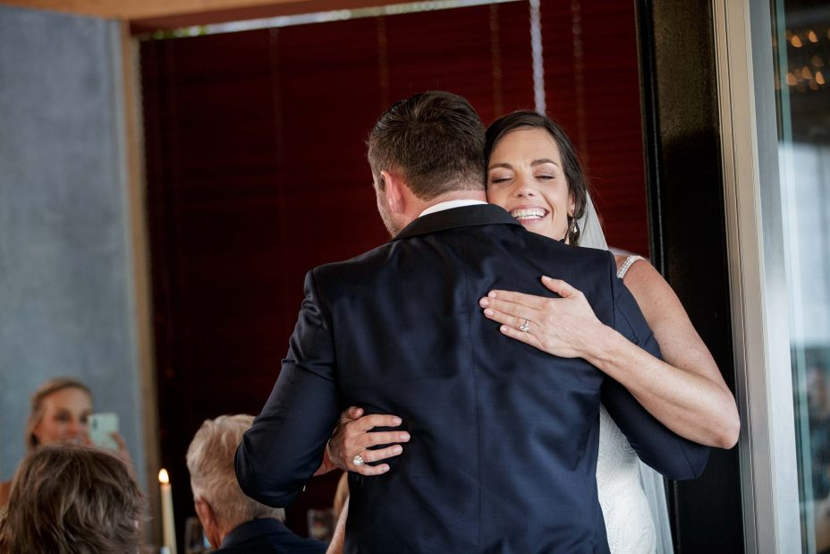 Bride and groom hugging after speeches during their wedding reception at KBB Kauri Bay Boomrock