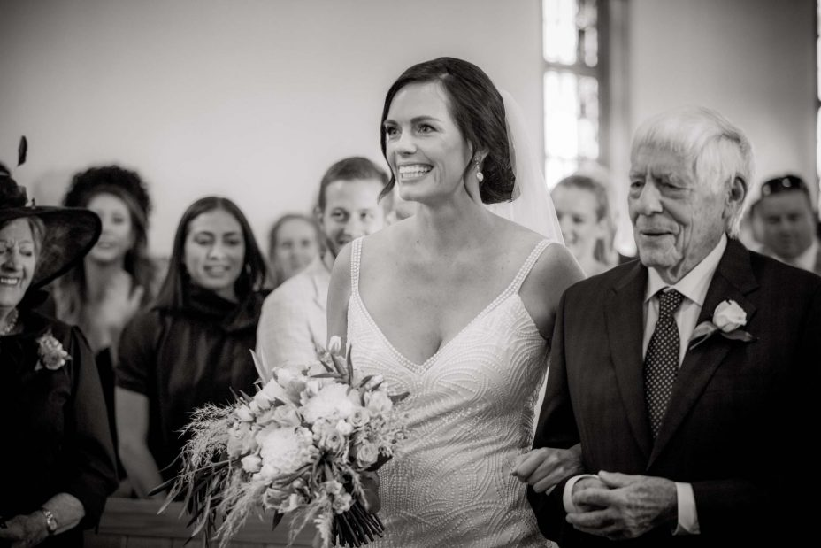 Bride walks down isle with her father at Saint Cuthbert's College chapel Auckland