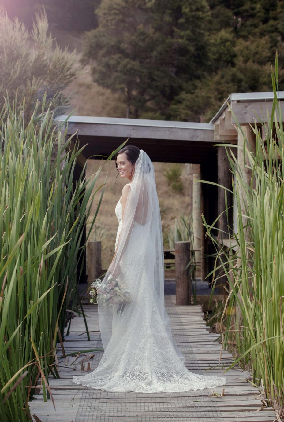 Bride in wedding dress and groom pose for photo in the reeds at the Bunker at Kauri Bay Boomrock