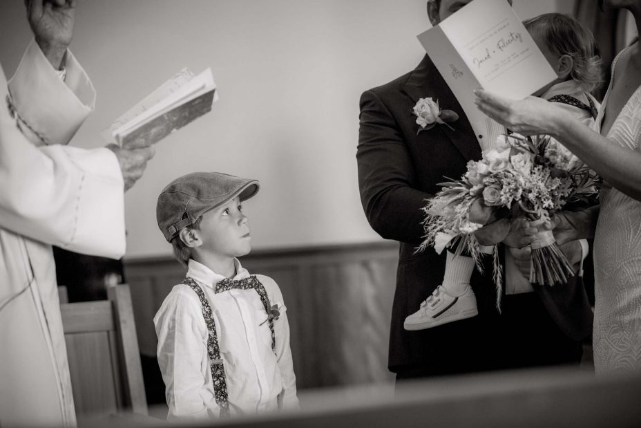 Cute pageboy on cloth cap looks up at bride and groom during wedding ceremony