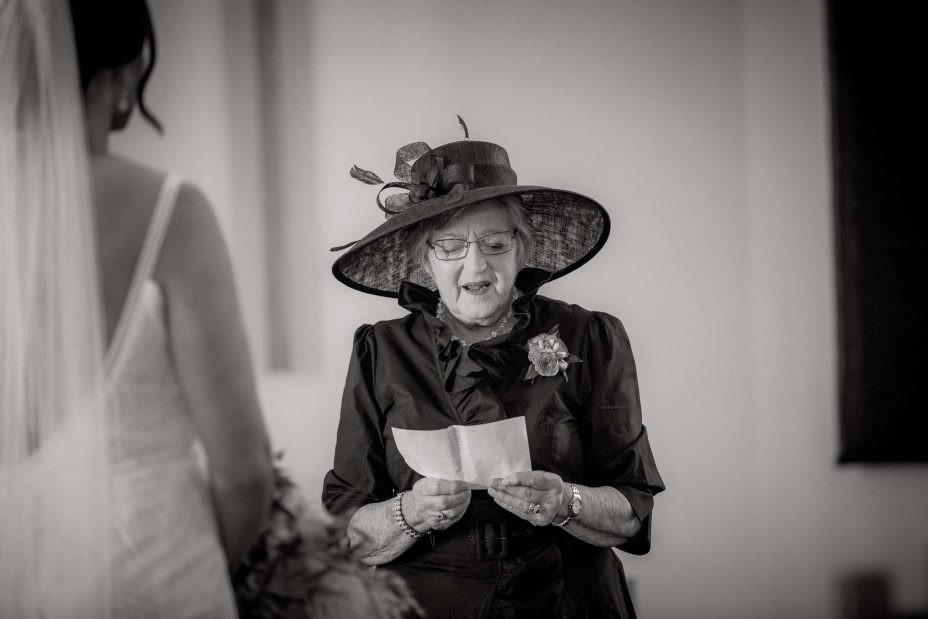 Bride's mother in big wedding hat reads at ceremony at st. Cuthbert's college Chapel reads