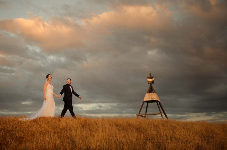 Bride & Groom walk over hill sunset at Kauri Bay Boomrock Clevedon