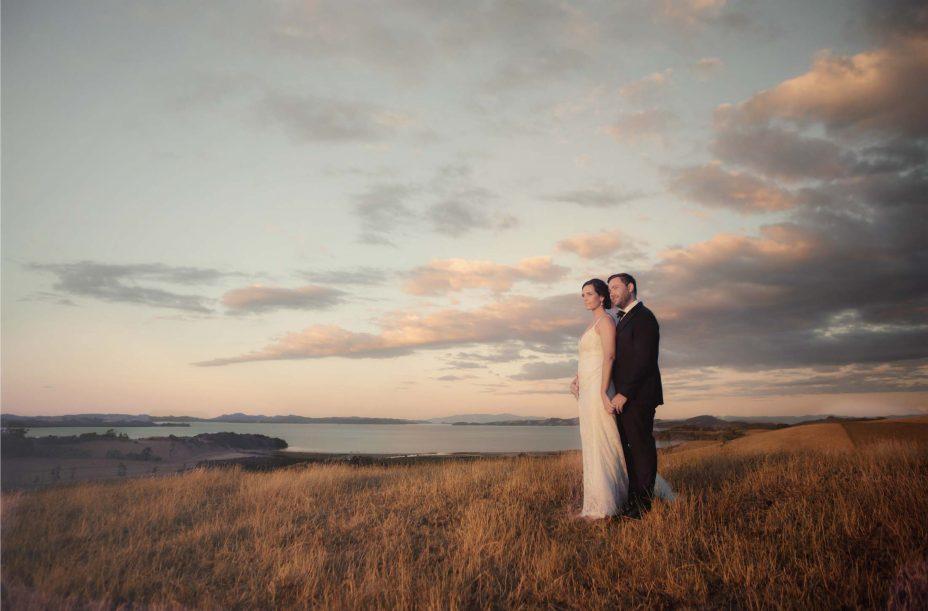 Bride & Groom walk over hill sunset at Kauri Bay Boomrock Clevedon