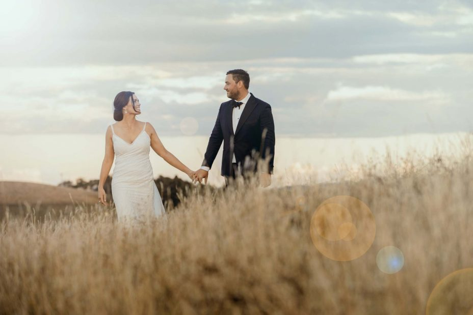 Bride & Groom walk over hill sunset at Kauri Bay Boomrock