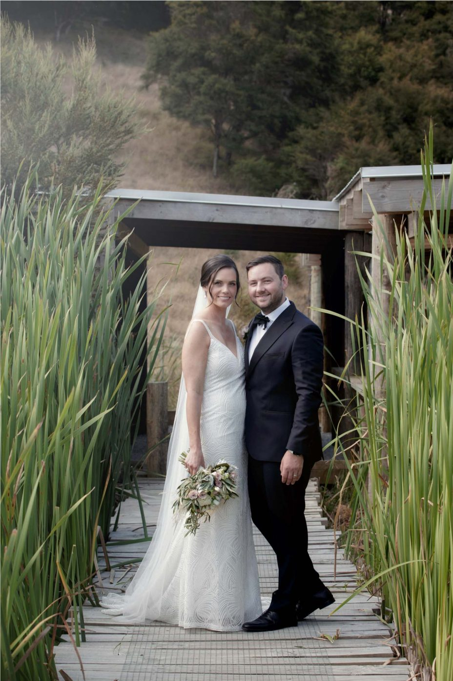 Bride and groom pose for photo in the reeds at the Bunker at Kauri Bay Boomrock