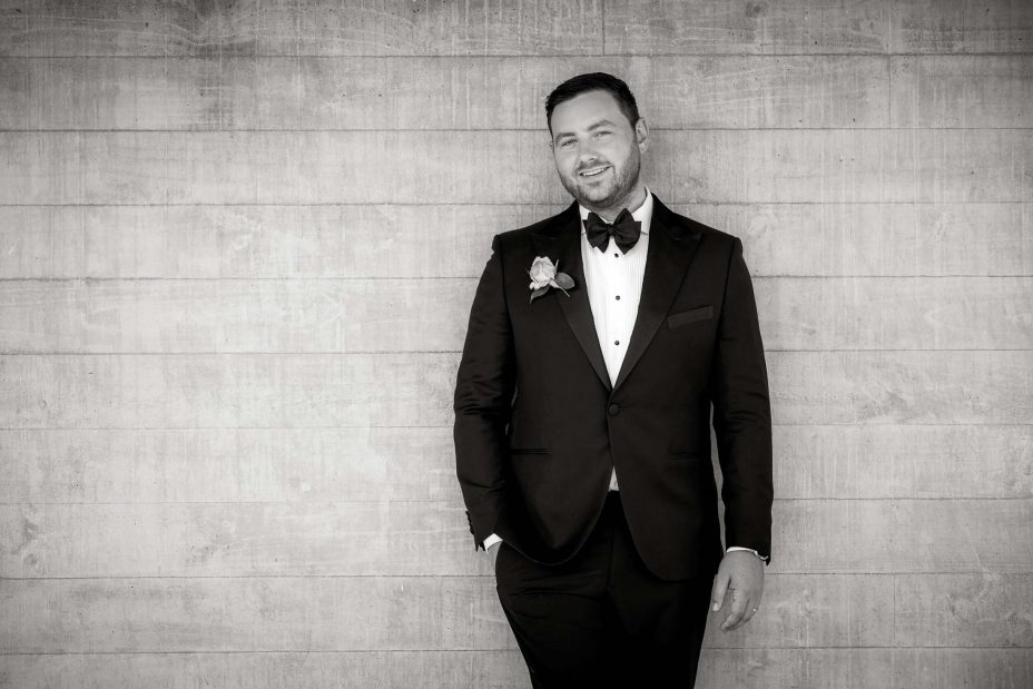 Bridegroom wearing bow tie poses for photo by concrete wall Kauri Bay Boomrock