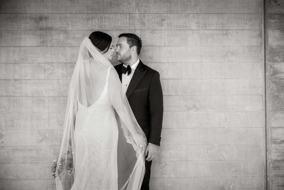 Bride and groom pose for photo by concrete wall Kauri Bay Boomrock
