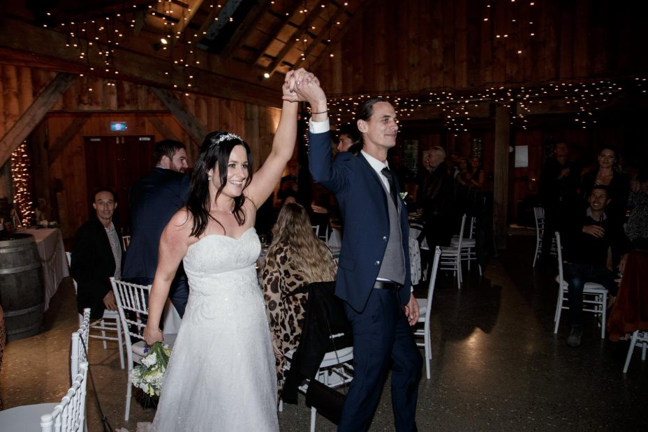 Brie and groom holding hands high enter wedding reception