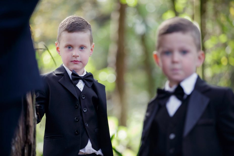 two young page boys in bow ties and black jackets at a wedding ceremony at Kumeu Valley Estate