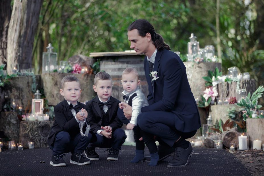 two young page boys and the groom wearing bow ties and black jackets at a wedding ceremony at Kumeu Valley Estate