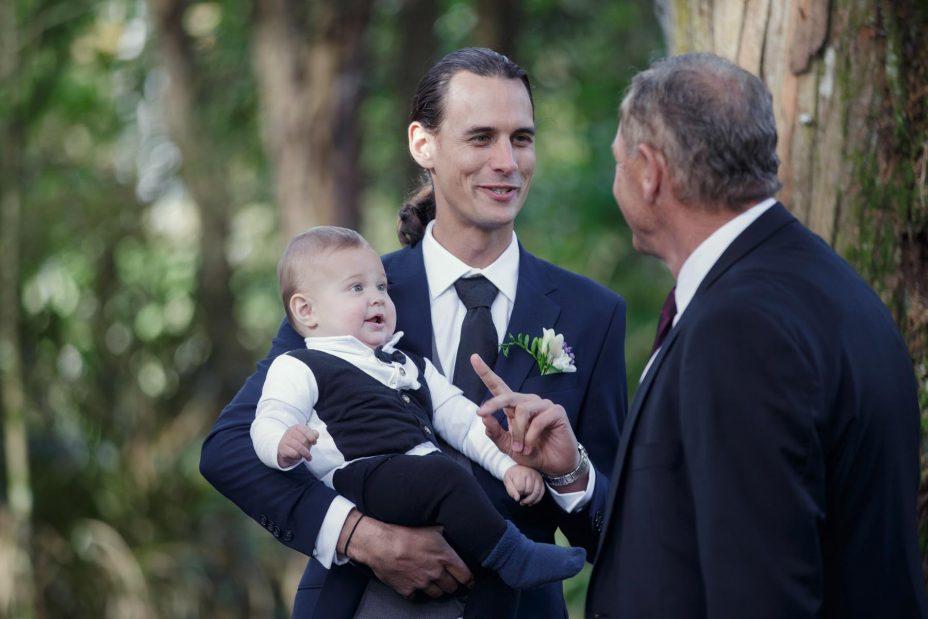 Wedding groom cradles his baby son
