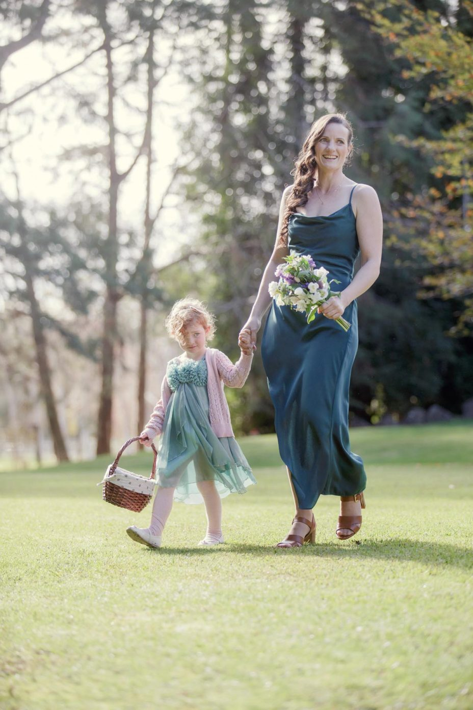 Bridesmaid and flower girl with flower basket walk to the wedding ceremony