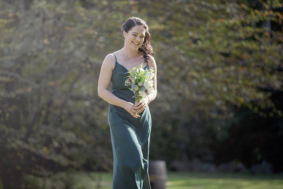 Bridesmaid in green dress wlaks slowly towards the ceremony