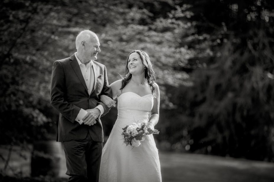 Bride laughs with her father as they walk together to her wedding ceremony