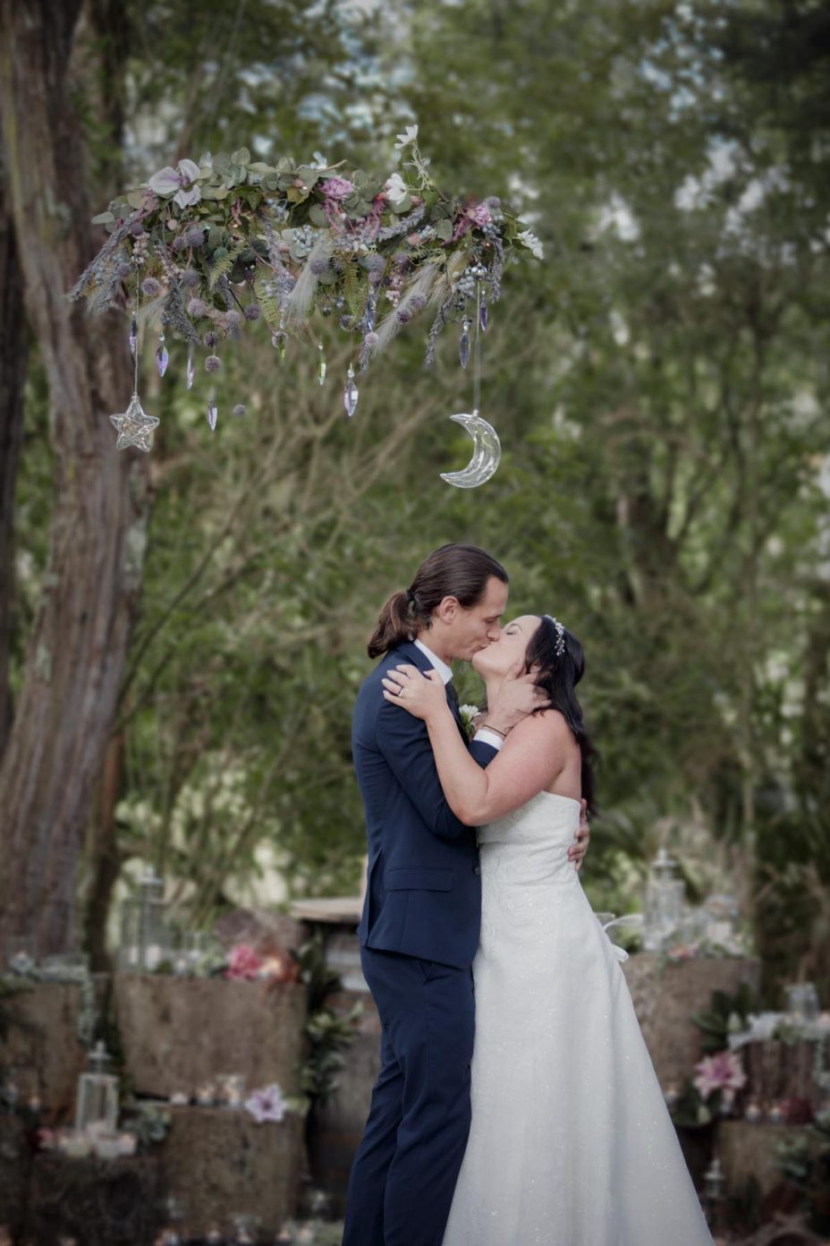 Bride and groom first kiss during ceremony at Kumeu Valley Estate