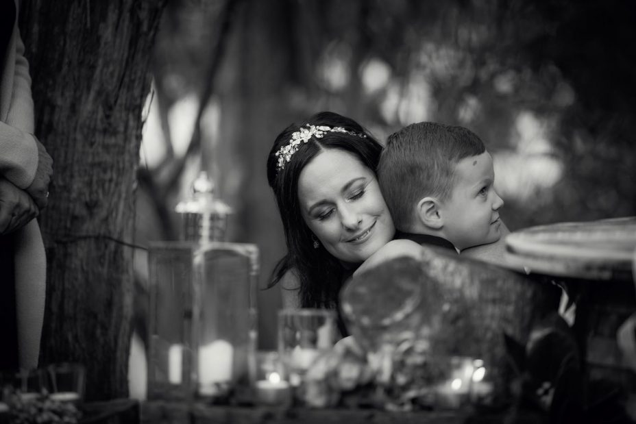 Bride cuddles little page boy at her wedding ceremony