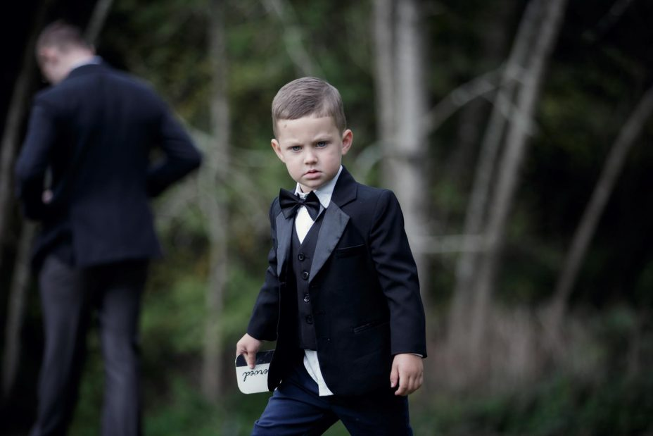 Little page boy wearing bow tie and black jacket at wedding
