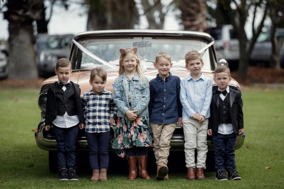 Children line up in front of American wedding car